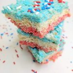 3 red, white, and blue rice krispie treats stacked on top of each other with sprinkles around them