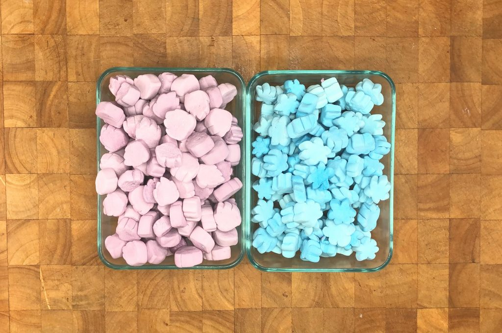 two separate bowls of blue snowflake and purple snowman head shaped marshmallows.