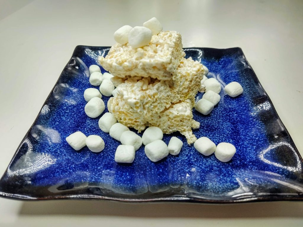 blue plate of frozen rice krispie treats with mini marshmallows sprinkled around