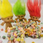 with 3 troll dolls behind them