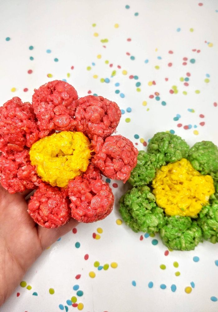 2 flower rice krispie treats. one with green petals and one with red petals
